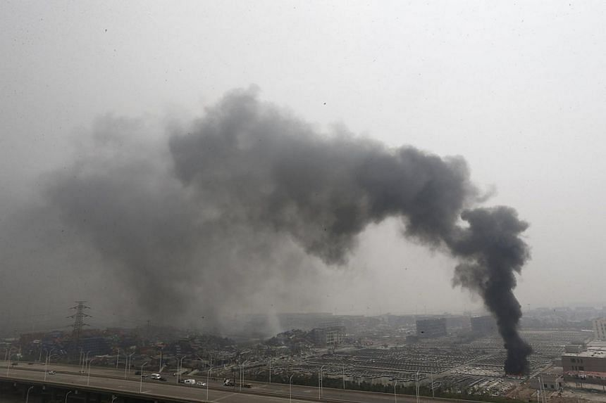 Smoke rises as damaged vehicles are seen burning near the site of Wednesday night's explosions, at Binhai new district in Tianjin, China on Aug 15, 2015.