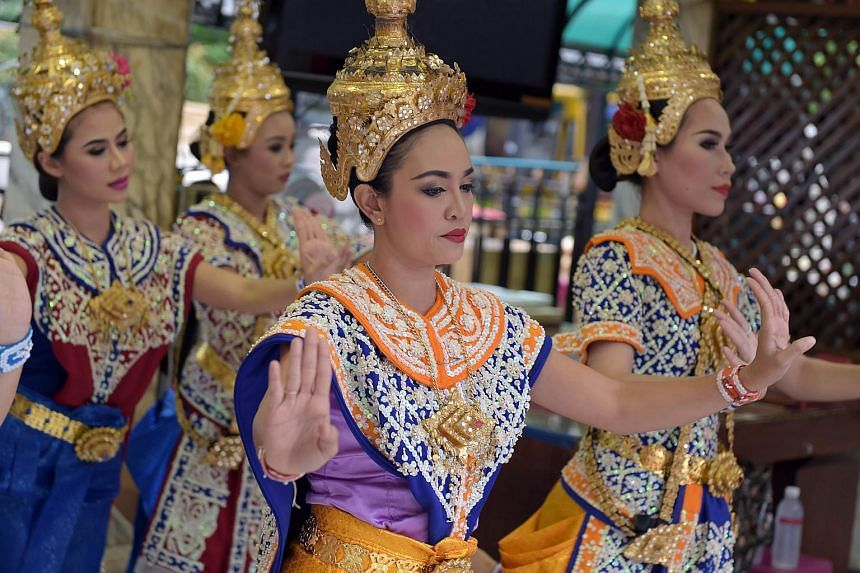 Thai shrine dancers perform at the reopened Erawan shrine in central Bangkok on Aug 21, 2015.