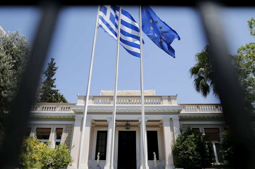 The Greek (left) and the European Union flags in front of the Prime Minister offices, in Athens, Greece.