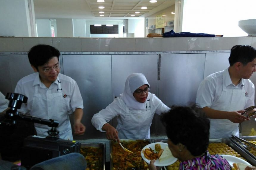 The PAP team for Marsiling-Yew Tee GRC (from left) Lawrence Wong, Halimah Yacob and Alex Yam serving lunch to residents at a Marsiling block party.