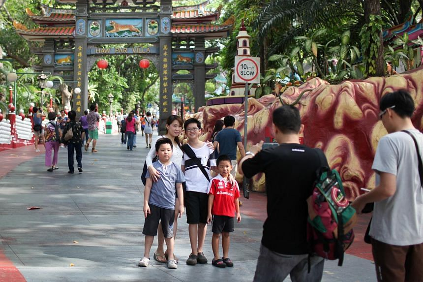 A family taking a photo in front of the entrance of Haw Par Villa.