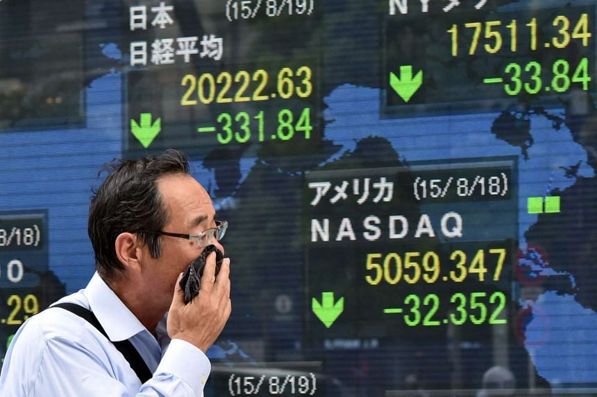 A man passing by a share prices board in Tokyo.