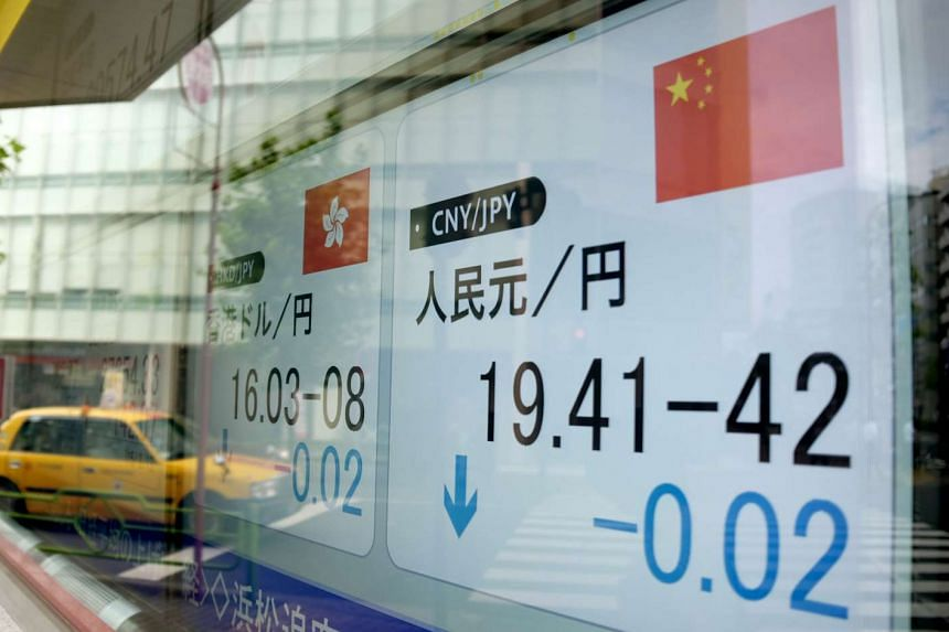 A foreign exchange rate board showing the Japanese yen against the Chinese yuan in Tokyo on Aug 13, 2015.