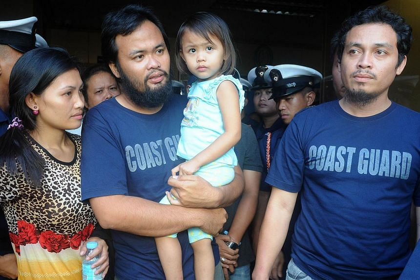 Philippine coastguards Rod Allain Pagaling (2nd left) and Gringo Villaruz (right) are reunited with their families in Manila on Aug 21, 2015.