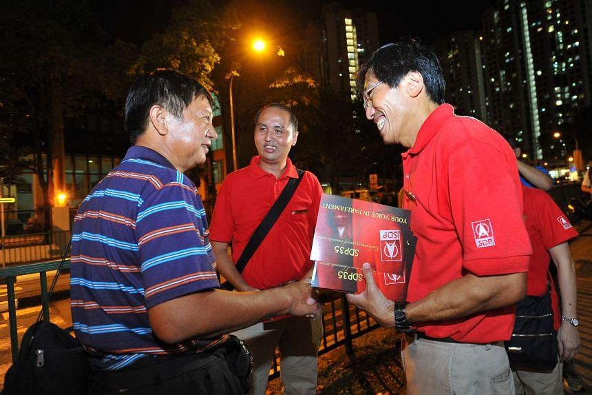 Dr Chee Soon Juan (right), Secretary-General of the Singapore Democratic Party, during an SDP walkabout and house visiting at Bukit Panjang on July 30, 2015.
