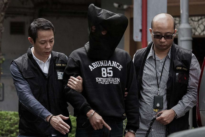 One of two alleged assailants (centre) of an attack on Mr Kevin Lau in a picture taken on March 18, 2014.