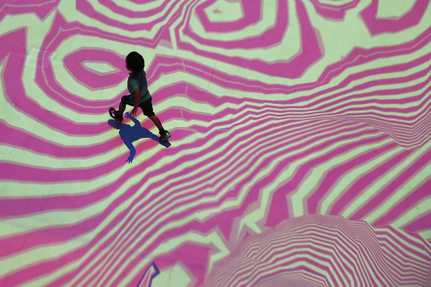 A boy runs across an interactive light installation display titled 'Pixel Wave 2015' by the artists Miguel Chevalier and designers Carolyn Kan and the label Depression during the start of the Singapore Night Festival 2015, on Aug 21, 2015.