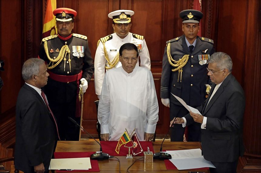 United National Party leader Ranil Wickremesinghe (right) taking his oaths as Prime Minister before Sri Lanka President Maithripala Sirisena (centre) on Aug 21, 2015.