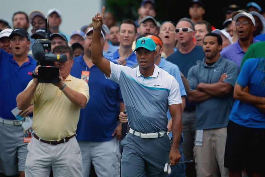 Woods reacts after chipping in for a birdie on the first hole during the first round of the Wyndham Championship.