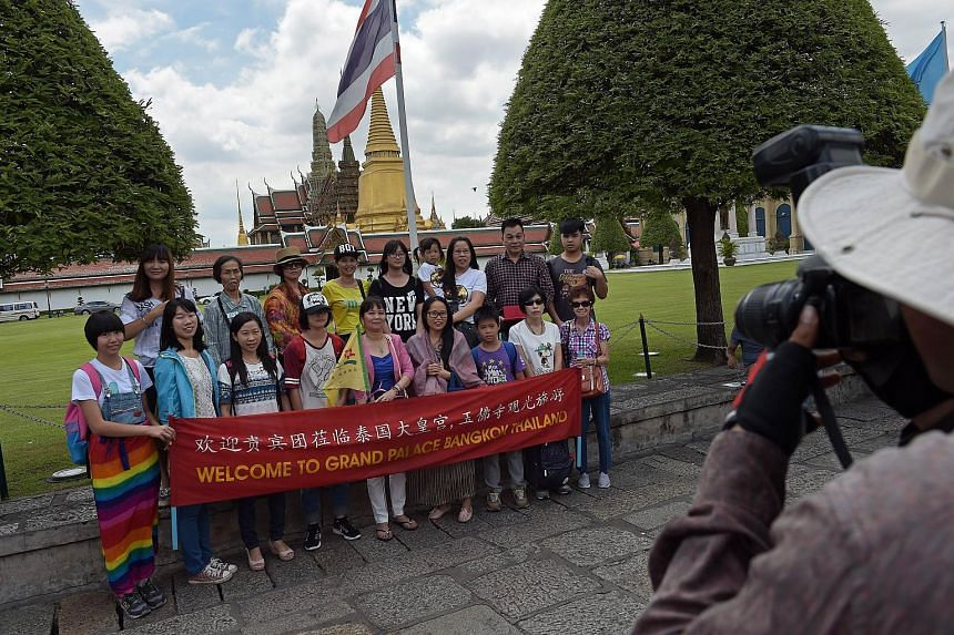 Chinese tourists pose for a group picture before visiting the Grand Palace in Bangkok on August 21, 2015.