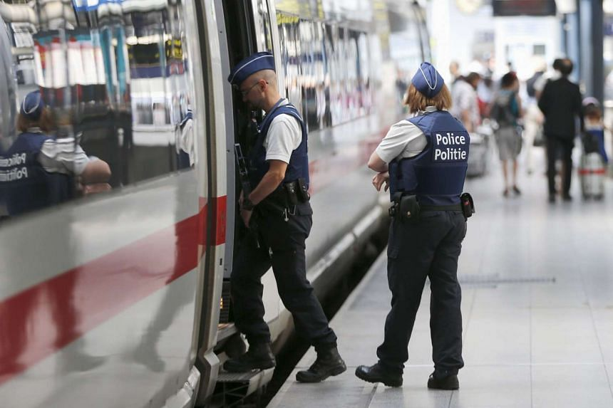 Belgian police officers enter a train during a patrol on Aug 22, 2015.