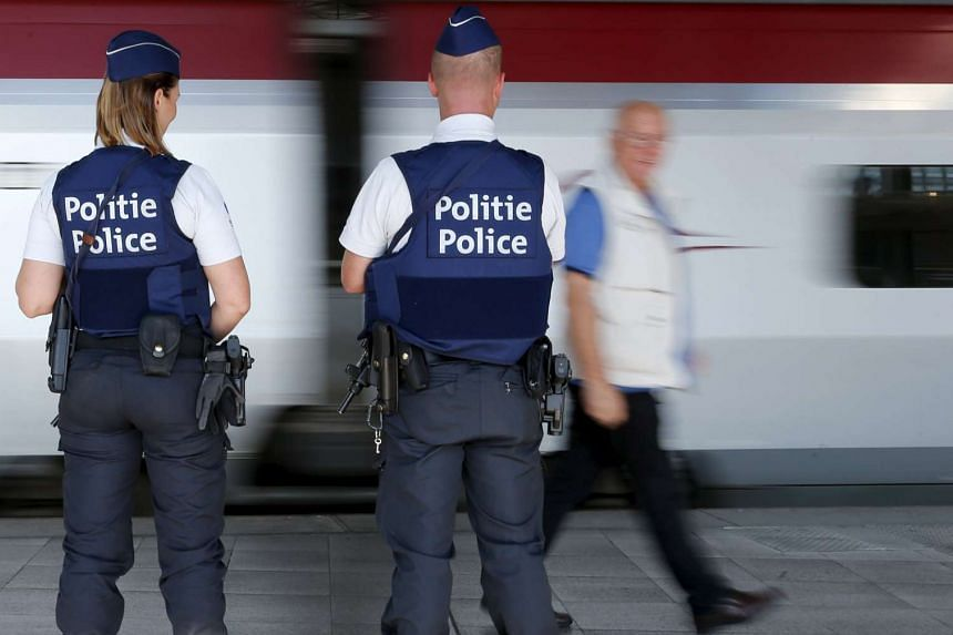 Belgian police officers stand guard at a rail station in Brussels on Aug 22, 2015.