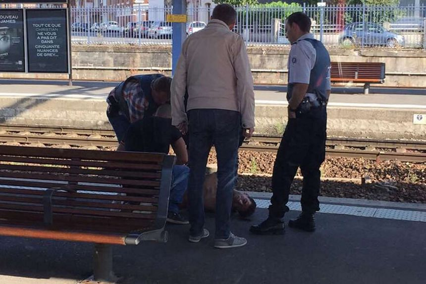 Police detaining a suspect on the platform after an armed gunman on the train was overpowered by passengers on Aug 21, 2015.