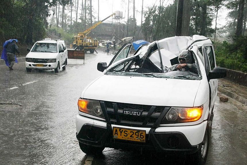 A resident driving a vehicle damaged by a fallen electric post after Typhoon Goni battered Baguio city in northern Philippines on Aug 21, 2015.