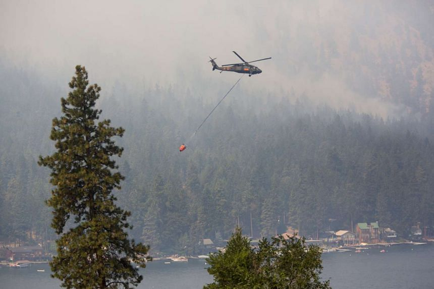 A Blackhawk military helicopter is used to make water drops during the First Creek Fire in Chelan, Washington, on Aug 21, 2015.