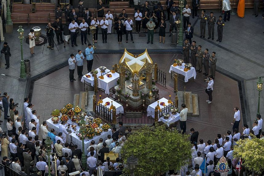 Thai government officials attending a religious ceremony at Erawan shrine, the site of Monday's deadly blast, in Bangkok yesterday. No party has claimed responsibility for the bomb attack. Police have released two people who turned themselves in for