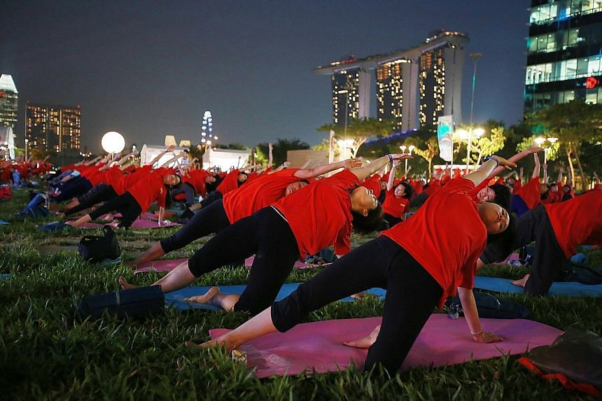 Participants at a mass yoga event at The Lawn @ Marina Bay - an open area above Marina Bay Link Mall. Thursday's fitness event drew about 500 people. It was organised by My Paper, the bilingual newspaper published by Singapore Press Holdings. Places