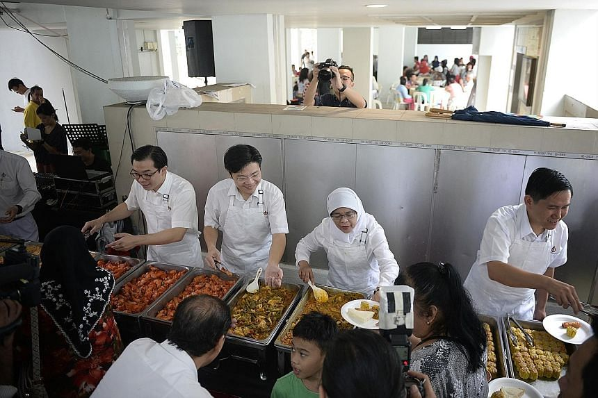 PAP candidates in Marsiling-Yew Tee GRC (from left) Ong Teng Koon, Lawrence Wong, Halimah Yacob and Alex Yam dishing out servings of fried rice, beehoon, sayur lodeh, chicken wings and siew mai to residents, many of them pioneers, at a block of renta