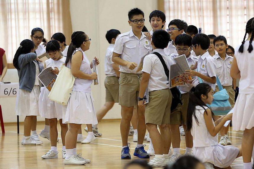 With the PSLE makeover, instead of getting a score out of 300 points, pupils will get grade bands. (Right) Kong Hwa pupils mingling on the day they received their PSLE results last year.
