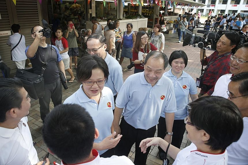Workers' Party leaders Sylvia Lim (third from left) and Low Thia Khiang greeting People's Action Party members during a walkabout at MacPherson Market and Food Centre on Aug 7.