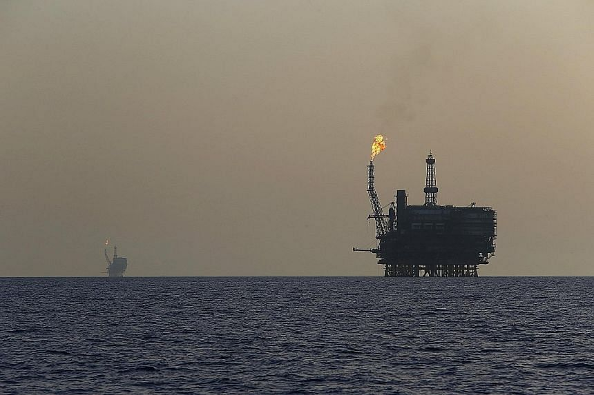 Offshore oil platforms at the Bouri Oil Field off the coast of Libya. The price of a barrel of oil has halved since June last year, reaching levels previously seen at the depths of the global financial crisis in 2009.