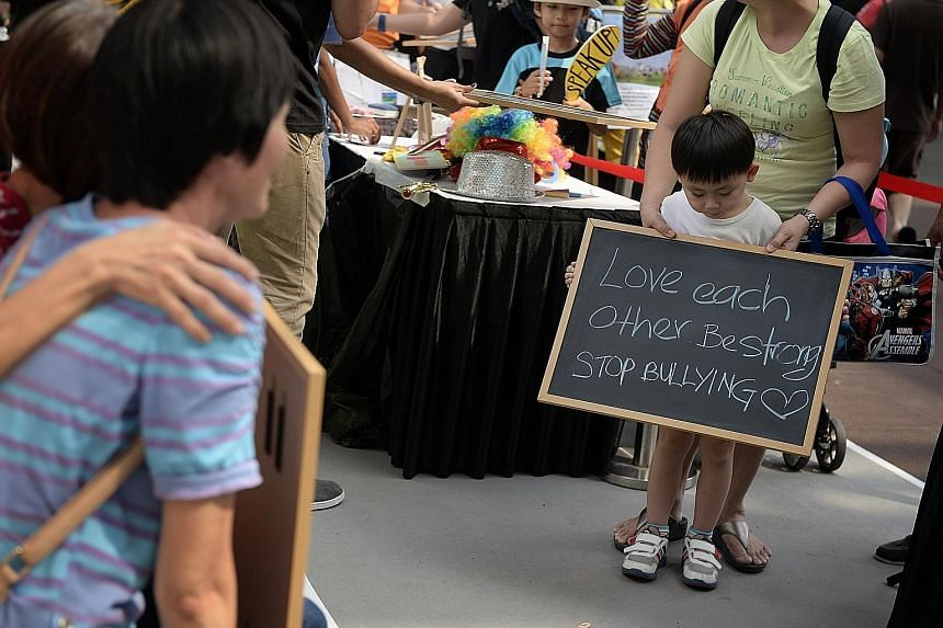 Six-year-old Max Wan doing his bit to spread the anti-bullying message at the Singapore Children's Society roadshow yesterday. With him is his mother Katherine Lim, 41.
