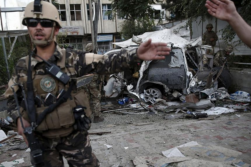 Members of Afghan security forces keep watch in front of a damaged car after a bomb blast on Aug 22, 2015.