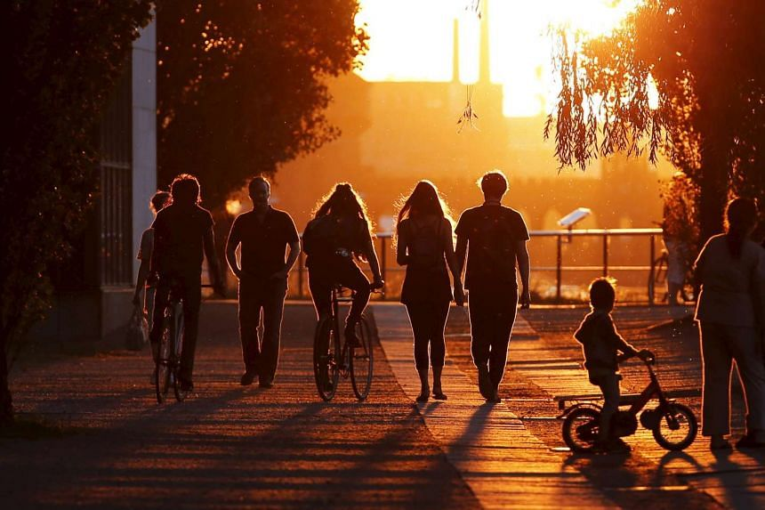 People walk by the River Spree at sunset in Berlin. Deaths in Germany outnumbered births in 2014.