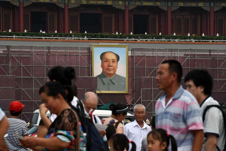 Tourists walking in Tiananmen Square in front of scaffolding next to the portrait of late communist leader Mao Zedong in Beijing.