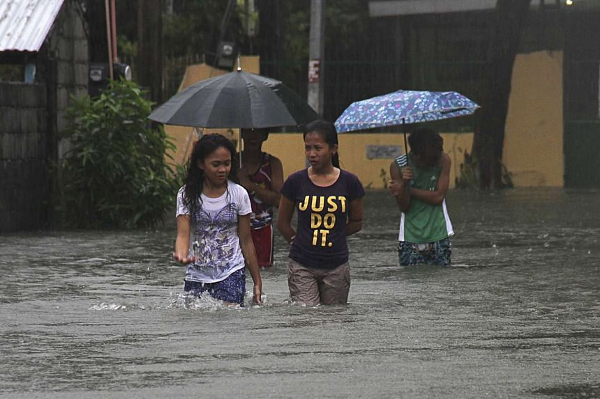 Residents wade across floodwaters caused by Typhoon Goni in Bacnotan, La Union, in the northern Philippines.