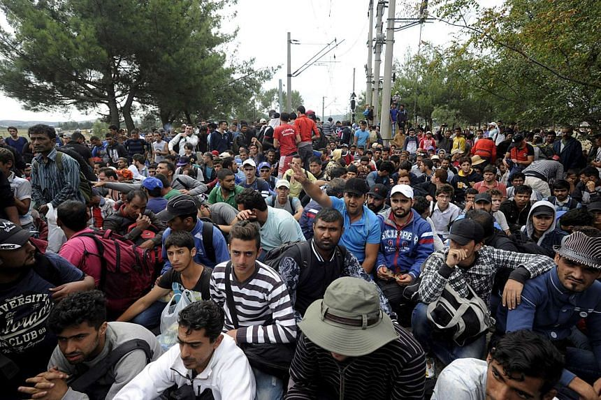 Migrants gather as they are stopped by Macedonian police at the Greek-Macedonian border on Aug 21, 2015.