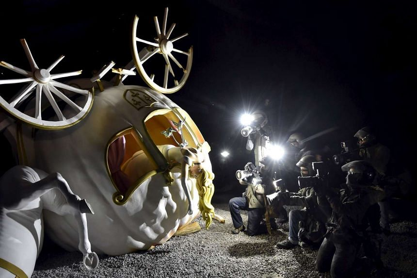 A carousel, a dead Cinderella hanging out of her crashed pumpkin carriage (above) and a boat filled with migrants at Dismaland.