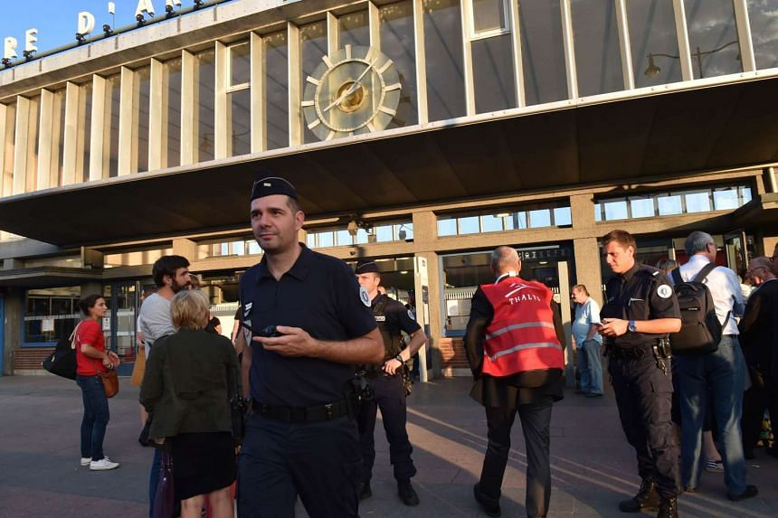 French police and train personnel stand outside the main train station in Arras, northern France.