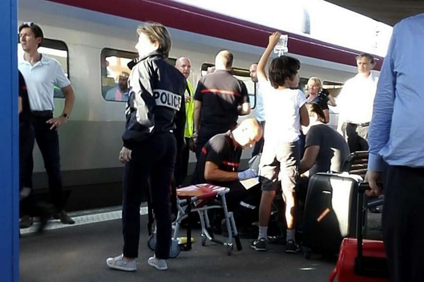 A police officer stands by as a passenger (R, seated) receives medical attention in Arras, northern France.