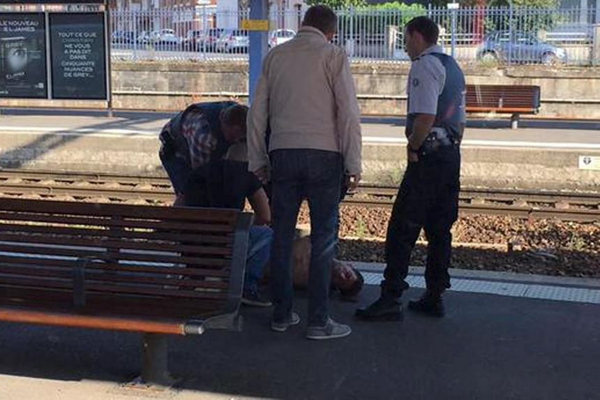 French police stand over a man who is apprehended on the platform at the Arras train station after after shots were fired on the Amsterdam to Paris Thalys high-speed train.