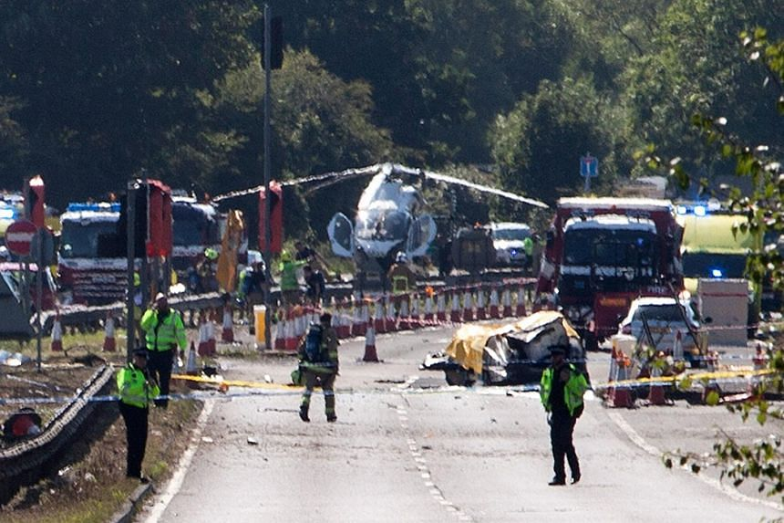Police and emergency services stand by the wreckage of the aircraft, believed to be a Hawker Hunter jet, that plummeted to the ground when it failed to pull out of a loop manoeuvre, smashing into in a huge fireball in the A27, West Sussex, Britain on