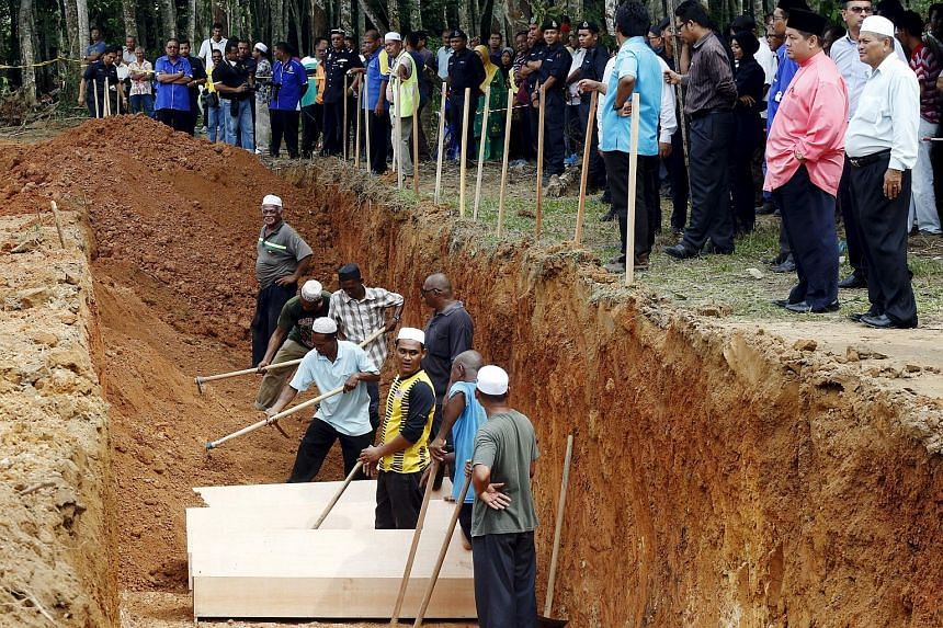 Men fill in a mass grave with coffins of unidentified remains of Rohingya people found at a traffickers camp in Wang Kelian in July, at a cemetery near Alor Setar, Malaysia.