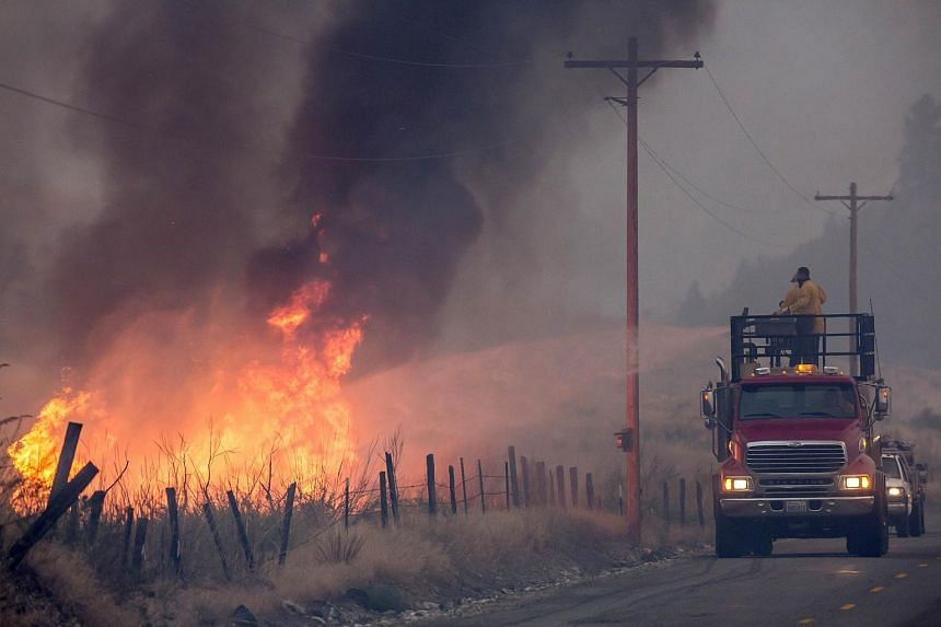A makeshift fire truck puts water on a wildfire, which is part of the Okanogan Complex, as it burns through brush on Aug 22, 2015 near Omak, Washington.