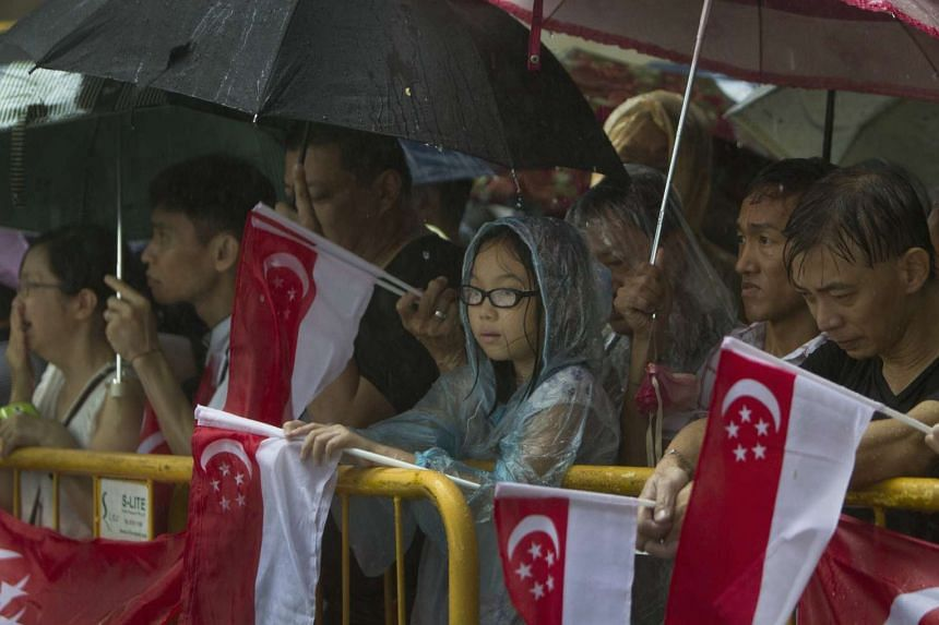 Singaporeans standing in the rain during the funeral procession of former prime minister Lee Kuan Yew.