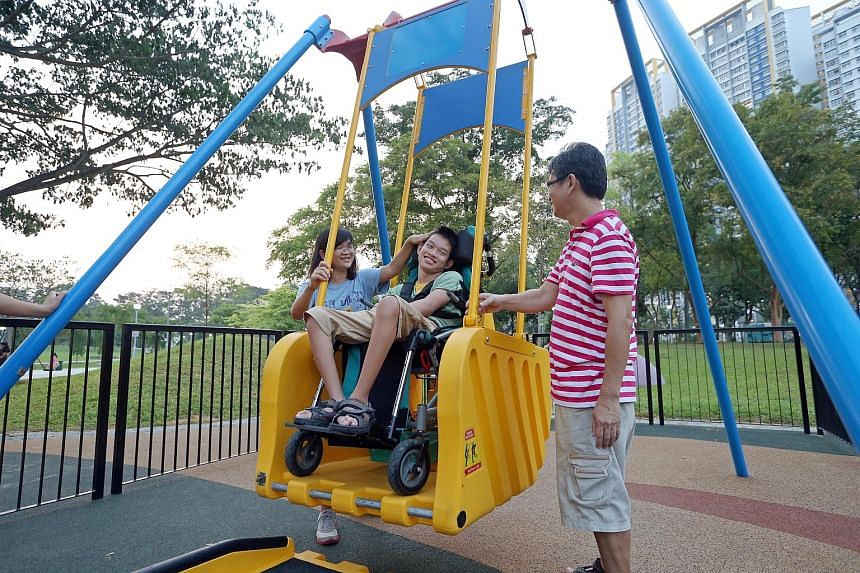Thirteen-year-old Samuel Chong, who was born with cerebral palsy, plays on a swing for the first time as his parents Amy Teo, 51, and Chong Choon Leong, 49, accompany him at Bishan-Ang Mo Kio Park yesterday. The family travelled from their home in Kh