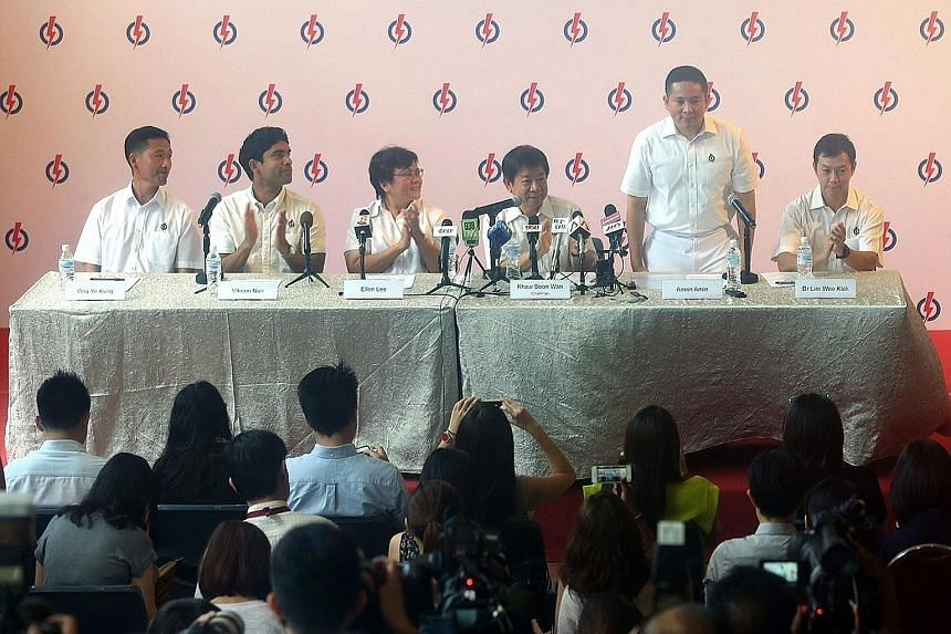 A new theme is emerging with new candidates. PAP newcomer Amrin Amin (standing) at a media conference.