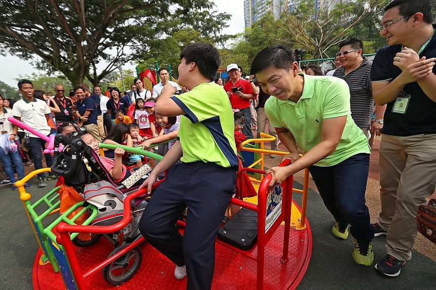 Fong Ruo En (above), six, trying out the special-needs friendly slide, which has rollers to stimulate the sense of touch and ease friction. Meanwhile, Minister Tan Chuan-Jin (right) gives the merry-go-round a good push, to the delight of a little gir