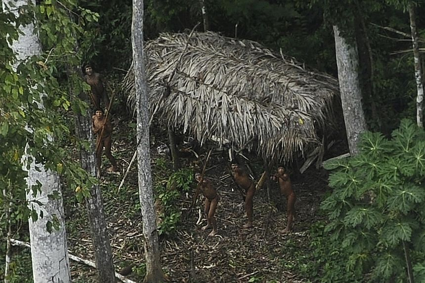 """Indians who are considered """"uncontacted"""" by anthropologists reacting to a plane flying over their community in the Amazon basin near the Xinane River in Brazil's Acre state, close to the border with Peru."""