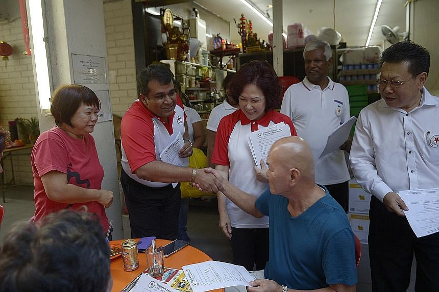 SPP's Lina Chiam and Ravi Philemon (both in white-and-red T-shirts) during the party's walkabout in Bukit Batok yesterday.