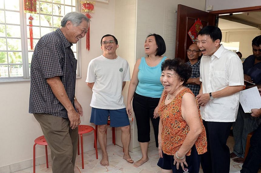 Minister for Defence and Bishan-Toa Payoh GRC MP Ng Eng Hen (left) and new People's Action Party (PAP) candidate Chee Hong Tat (right, in white shirt) visiting the home of Mr James Tan (in blue shorts), 34, and his family on Aug 10.