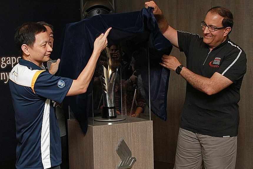 SIA chief executive Goh Choon Phong (left) and Second Minister for Trade and Industry S. Iswaran unveil this year's Formula One Singapore Grand Prix trophy.