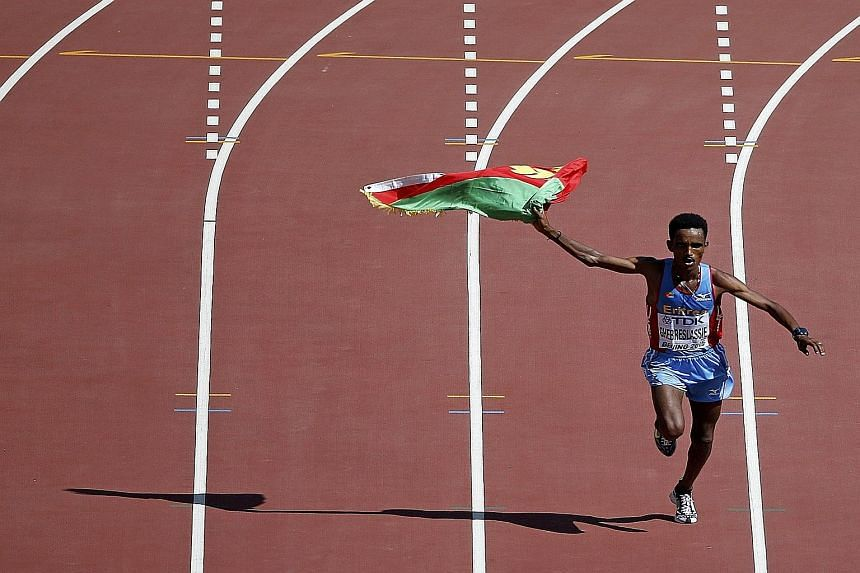 Ghirmay Ghebreslassie of Eritrea celebrates as he enters the Bird's Nest stadium to win the men's marathon after taking the lead from the 36km mark.