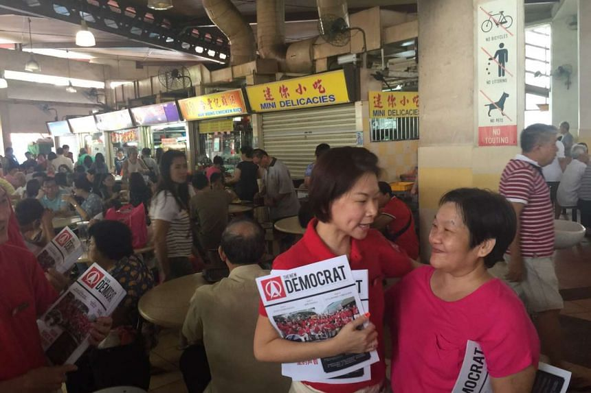 Entrepreneur Jaslyn Go, who was introduced by the Singapore Democratic Party's Chee SIok Chin as its candidate for Yuhua SMC earlier, speaking to a resident during a walkabout on Sunday.
