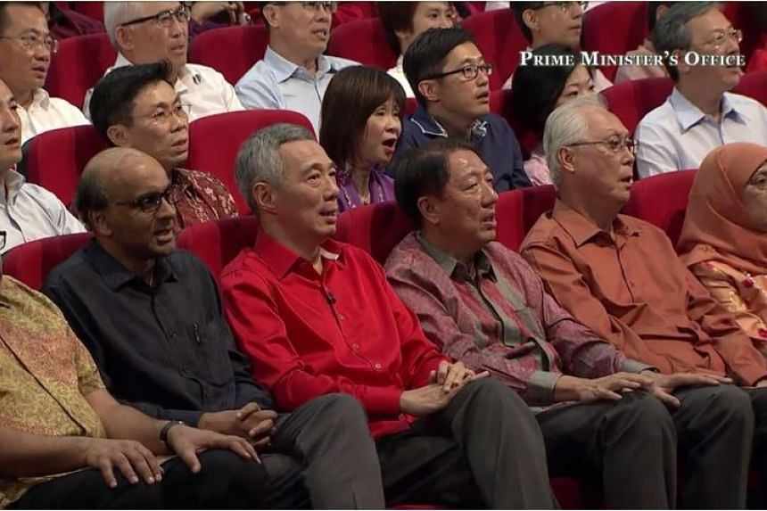 Prime Minister Lee Hsien Loong (in red), together with (from left) Deputy Prime Minister Tharman Shanmugaratnam, Deputy Prime Minister Teo Chee Hean and Emeritus Senior Minister Goh Chok Tong, singing Home during the performance by Kit Chan.