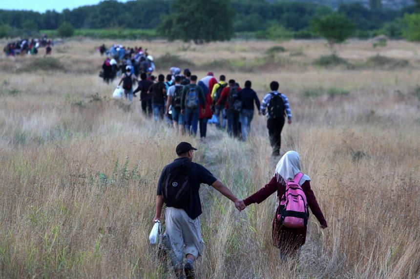 Migrants pass through the border from Greece into Macedonia near the town of Idomeni, Northern Greece.